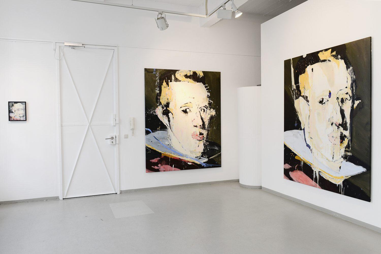 Innenansicht eines Galerieraums. Es sind zwei über Eck gehängte große Gemälde mit Porträtdarstellungen zu sehen.
